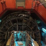 The ALICE experiment uses the 10,000-tonne ALICE detector – 26 m long, 16 m high, and 16 m wide – to study quark-gluon plasma. The detector sits in a vast cavern 56 m below ground close to the village of St Genis-Pouilly in France, receiving beams from the LHC.